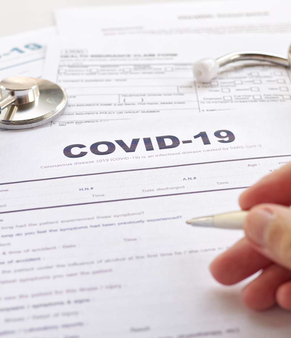 "COVID-19 Health insurance concept. Blurring of hand holding pen and Stethoscope on health form. Focus on "" COVID-19 """