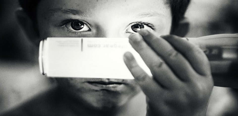 A grayscale photo of a boy holding a light close to his eyes.